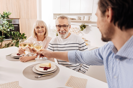 Mature man greeting his parents with wedding anniversary at home