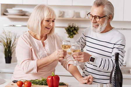 Lively aged marrieds enjoying champagne in the kitchen Stock Photo