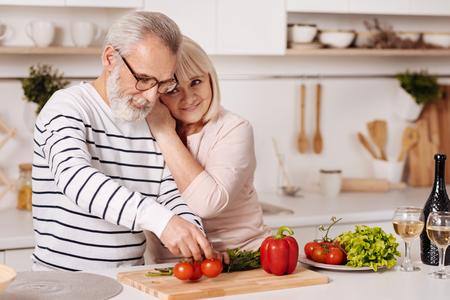 Cute elderly couple preparing family dinner in the kitchen