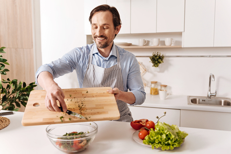 Satisfied bearded man cooking vegetable salad at home