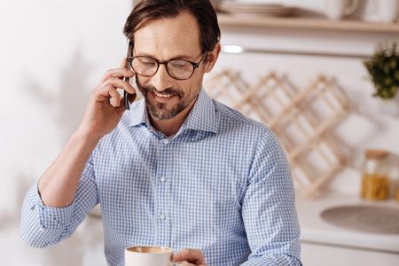 Optimistic freelancer enjoying phone conversation at home