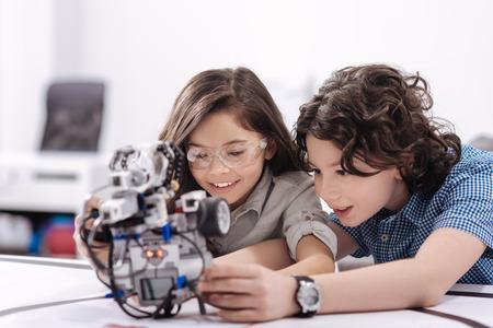 好奇心が強い子供が学校でロボットと遊ぶ