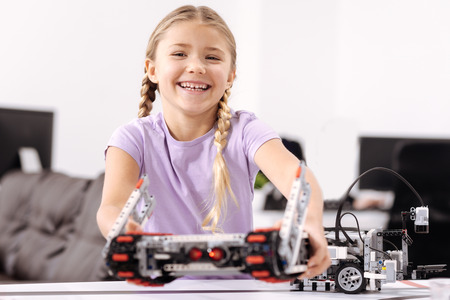 Amused girl representing science project at school Stock Photo
