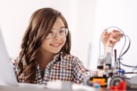 Smiling girl expressing positive emotions in the science studio Stock Photo