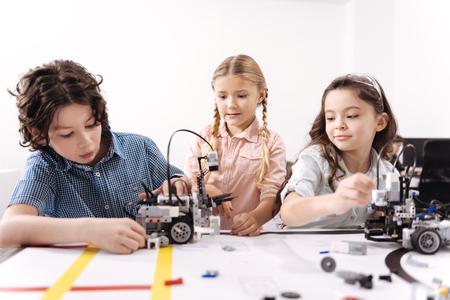 Alegres amiguitos trabajando en el proyecto de tecnología en la escuela