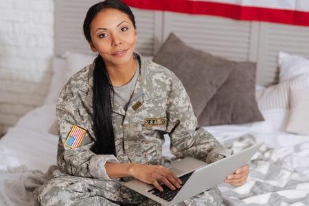 Ontspannen charmante vrouwenzitting op bed met haar laptop