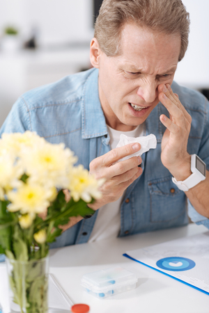 nasal: Sick male person sitting at workplace