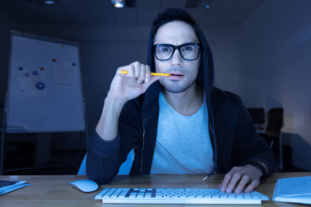 Handsome thoughtful hacker breaking into a website
