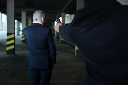 abducted: Angry male criminal aiming at the businessman Stock Photo
