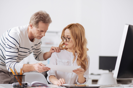 Busy aging manager touching young colleague in the office Stock Photo