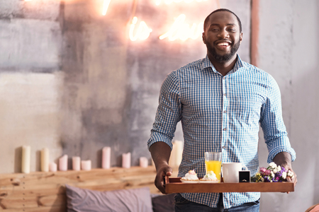 Charismatic African American man holding breakfast tray in the bedroom