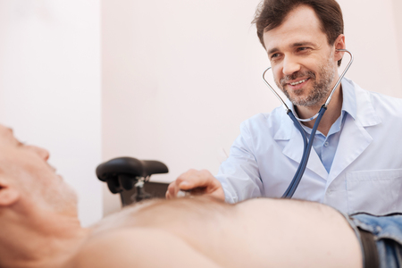 gerontology: Friendly distinguished specialist examining patients chest