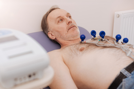 Focused calm man having his heart rate examined