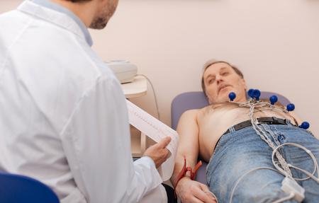 Especialista prominente que lee los resultados del ecocardiograma Foto de archivo