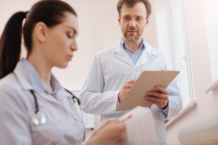 Skillful precise doctor seeking colleagues consultation