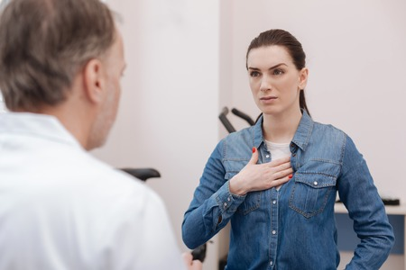 Worried young woman complaining about pain in the chest