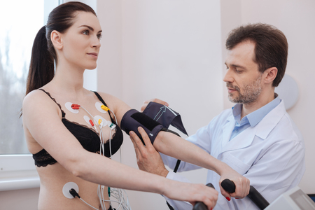 tonometer: Competent modern doctor using special tools for measuring blood pressure Stock Photo
