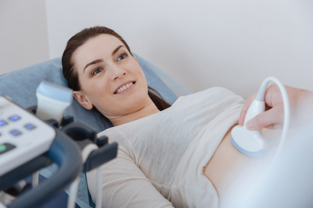 Pleased adorable woman lying on medical bed during the procedure