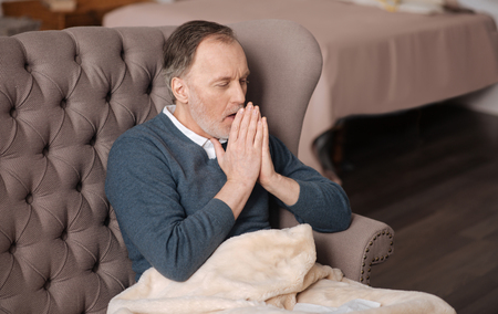 gerontology: Old man coughing while sitting on couch