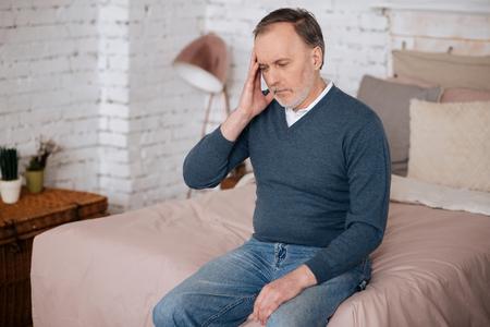 Old sitting man with headache