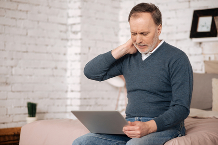 Old man having neckache while using laptop