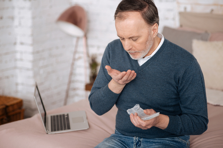 Top view of senior man taking pills Stock Photo