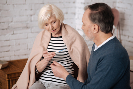Senior woman checking temperature near her husband