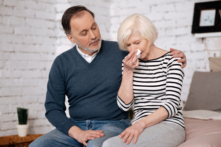 Senior woman blowing her nose near husband Stock Photo