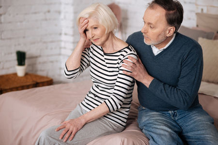 Man giving solace to his senior wife with headache