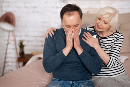 Senior man sneezing near wife