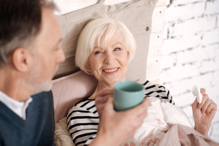 Closeup of senior lady taking tea from her husband Stock Photo