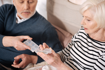 Closeup of old man giving pills case to his sick wife