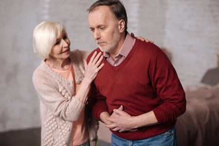 Elderly lady supporting her husband with stomachache