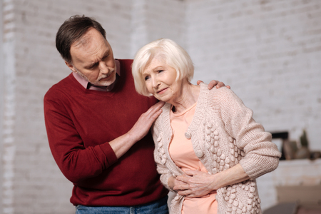 gerontology: Senior man supporting his wife with stomachache.