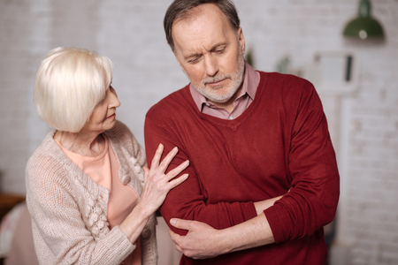 Senior lady taking care of husband with stomachache