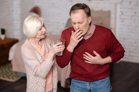 Aged man coughing while his wife helping him