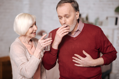 Senior man coughing and his wife helping him Stock Photo