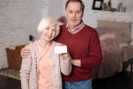 Happy elderly fmily holding card. Stock Photo