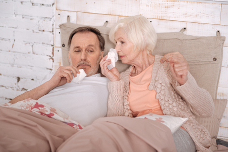 hankie: Elderly couple lying on bed with cold