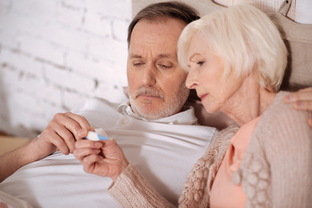 Close up of aged couple checking thermometer