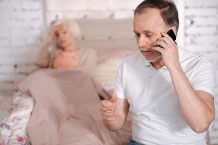 gerontology: Senior man calling emergency for sick wife
