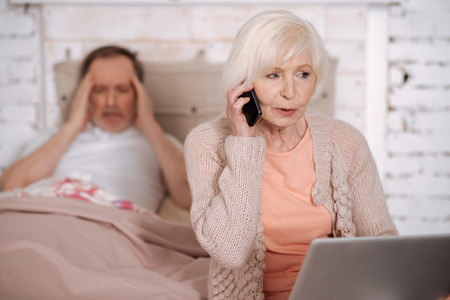 Elderly lady calling emergency for ill husband Stock Photo