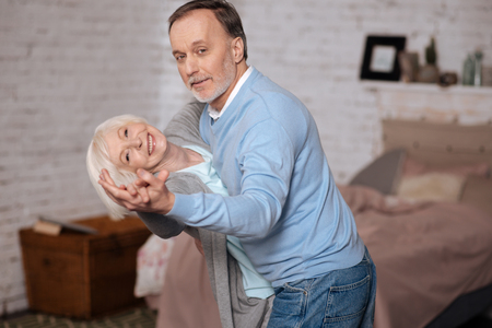 Aged man and woman are dancing together