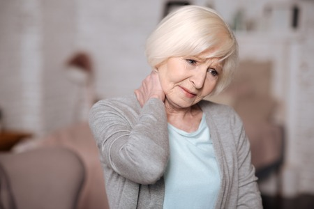 Close up of sad senior lady with neckache Stock Photo