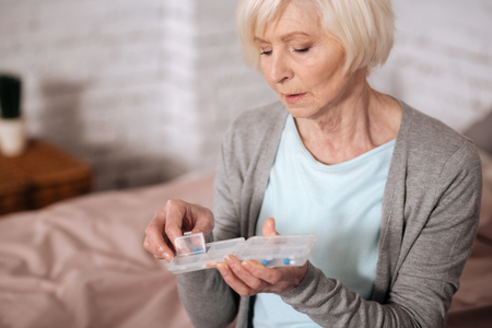Close up of elderly woman holding pills case
