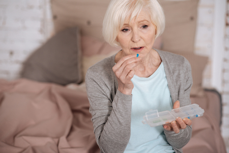 Sad aged woman taking pill
