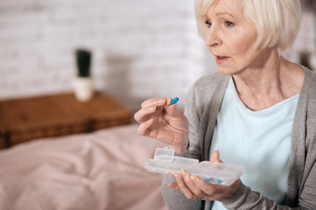 Side view of senior woman taking pill Stock Photo