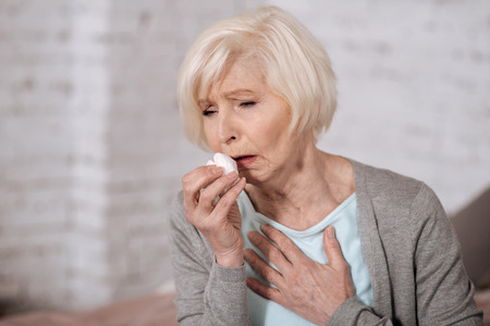 Closeup of elderly coughing woman Stock Photo