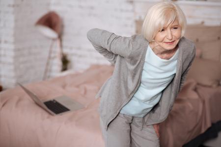 Elderly woman standing with backache