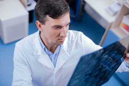 Serious experienced doctor holding the radiograph